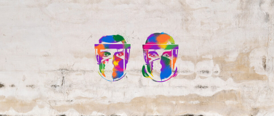 Masked faces are stenciled onto a wall in a rainbow of colors