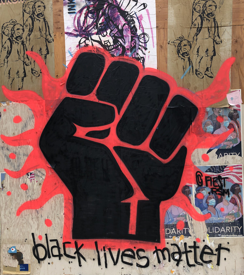 """Graffiti style artwork of a black first with red lines of energy running through it with the words """"black lives matter"""" underneath"""