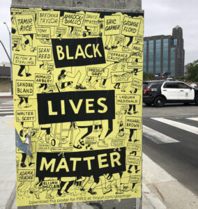 """A large poster that says """"BLACK LIVES MATTER"""" over a background of illustrated legs marching alongside the names of Black Americans killed by police or in police custody"""