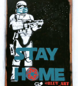 """A Star Wars stormtrooper wearing a medical mask with the words STAY AT HOME underneath. (The """"O' is the logo the Empire from Star Wars.)"""
