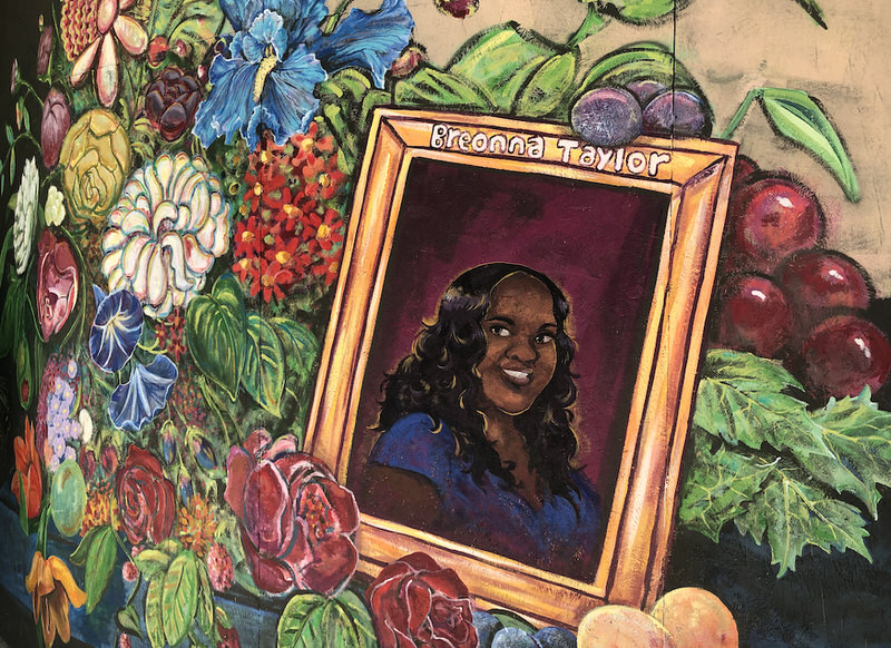 A mural of a smiling Breonna Taylor in a gold frame nestled in a bed of colors in numerous hues.