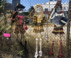 Life-size crocheted characters from the movie Clueless wearing medical masks masks