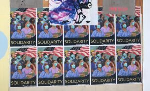 Posters of essential workers (doctors, nurses, construction, security, maintenance, retail) in front of a U.S. flag wearing masks, with the word SOLIDARITY underneath.