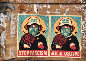 Posters of a woman in front of a chain-link fence holding roses, wearing a mask that says VOTE! and a hat that reads WE ARE HUMAN. A bold red bar at the bottom says STOP FASCISM. A Spanish version hang next to the English version.
