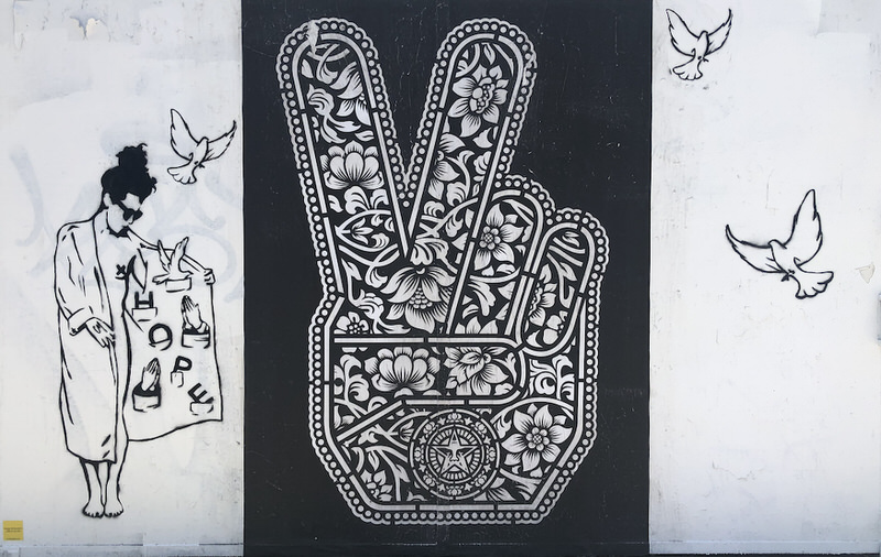 A large floral-patterned peace hand sign by Shepard Fairey with LA Hope Dealer's trench-coated woman and doves surrounding it.