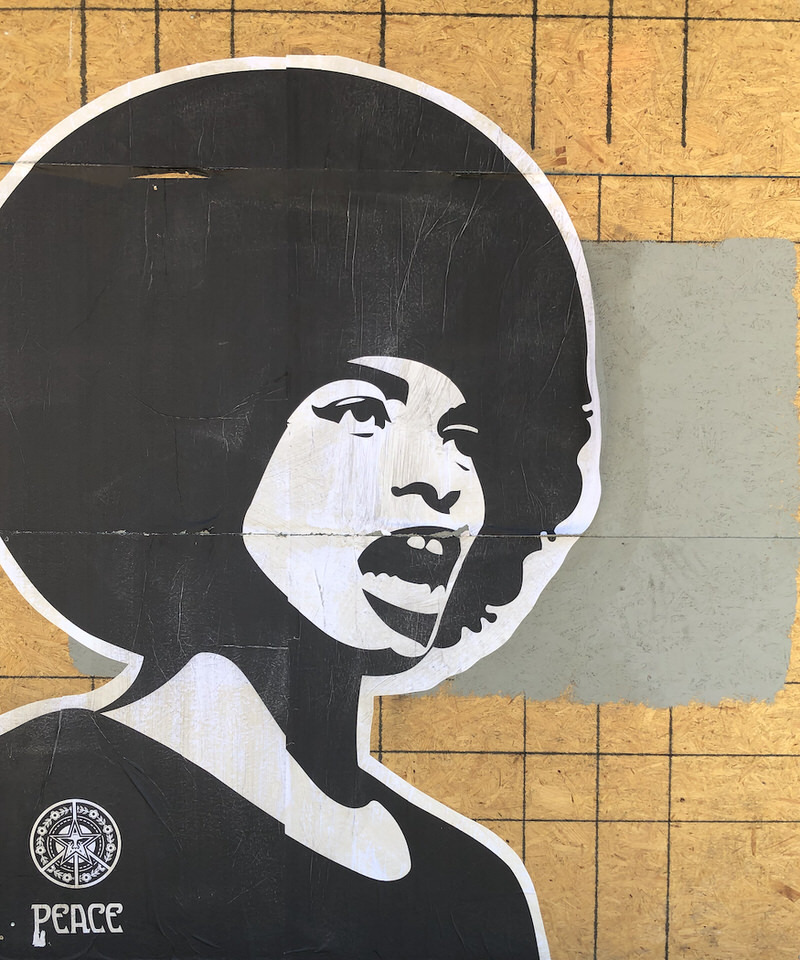 A large black-and-white image on a plywood barrier of a woman of color speaking