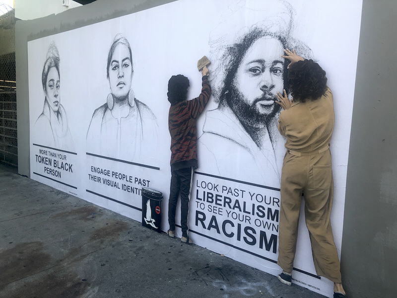 """A mural with realist black-and-white sketches of people of color accompanied by messages like """"Look past your liberalism to see your own racism."""" Freestanding representations of two artists appear to be placing the images onto the wall."""
