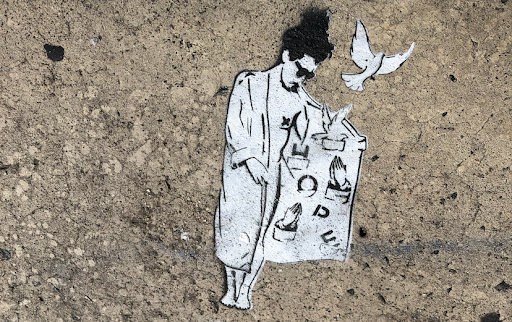 Stenciled sidewalk art of a woman opening a trench coat with the word HOPE inside and doves flying out.
