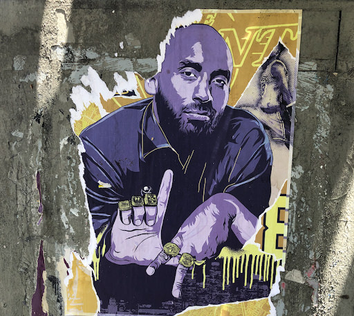 A poster of Kobe Bryant in purple and gold, holding his fingers to form the letters L.A. with championship rings on his fingers