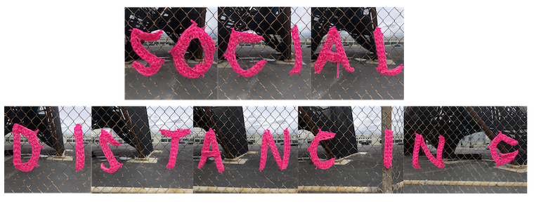 The words SOCIAL DISTANCING crocheted in pink across a long stretch of fence