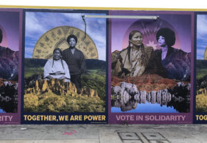"""Wall size images featuring photographs of indigenous and Black women side by side, collaged into natural landscapes, with the text underneath """"TOGETHER, WE ARE POWER"""" and """"VOTE IN SOLIDARITY"""". (Artwork by Mer Young.)"""