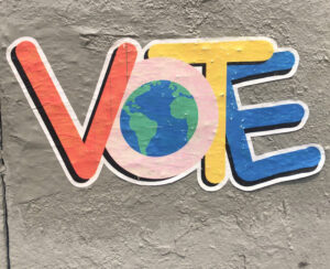 A giant sticker says VOTE in multiple colors with a globe in the middle of the O.