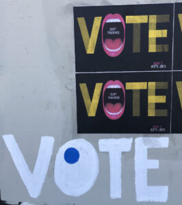 """A wall with posters and hand-painted art that read """"VOTE"""""""