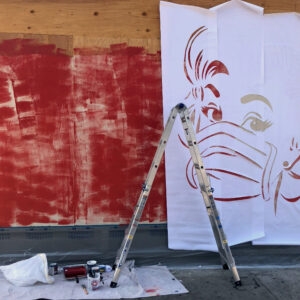 A plywood barrier with a large stencil attached to it and a ladder against it, as the artwork is being created.