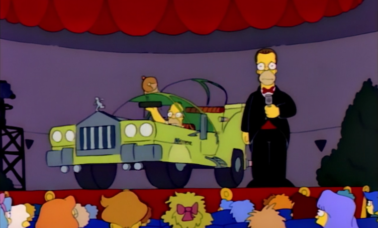 Homer sits in a bizarre looking green car while Herb stares out in embarrassment