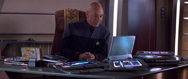 Jean Luc Picard sits at a desk covered in tablet devices