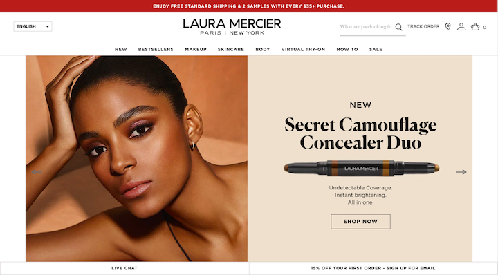 A screenshot from the Laura Mercier site, with a low-contrast background and photograph of a model accompanied by a serif font headline